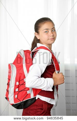 Beautiful little girl in school uniform with backpack