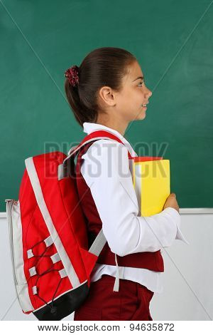 Beautiful little girl standing near blackboard in classroom
