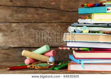 Stack of books and stationery on wooden background