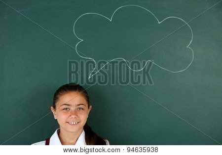 Beautiful little girl standing near blackboard