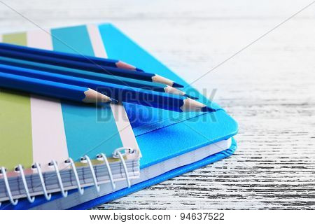 Turquoise crayons and diary on wooden table, closeup