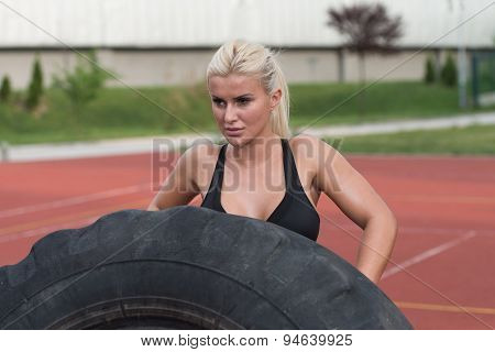 Young Man Doing Tire Flip Workout Outdoor