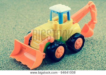 Tractor Backhoe Toy On Sand Background.