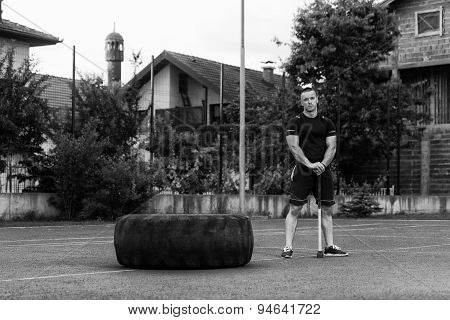 Young Man With Hammer And Tire Resting