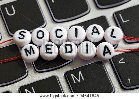 Social media letter beads on laptop keyboard keyboard concept for social networking, blogging, marketing and youth culture