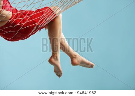 Close-up on the legs of a woman in red dress lying in a hammock on blue background