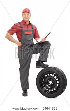 Full length portrait of a young mechanic holding a clipboard and looking at the camera isolated on white background