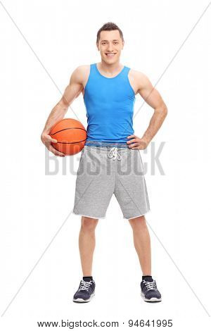 Full length portrait of a young athlete in a blue jersey holding a basketball and looking at the camera isolated on white background