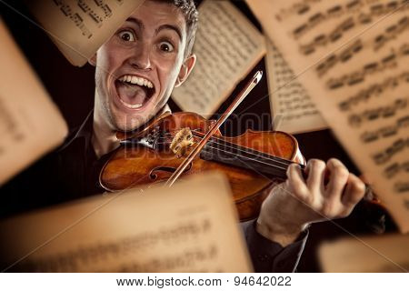 Young man with violin and flying notes on dark background