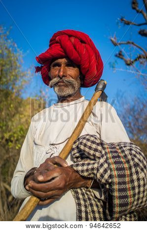 GODWAR REGION, INDIA - 13 FEBRUARY 2015: Rabari tribesman holds traditional axe on field and watches herd. Rabari or Rewari are an Indian community in the state of Gujarat.