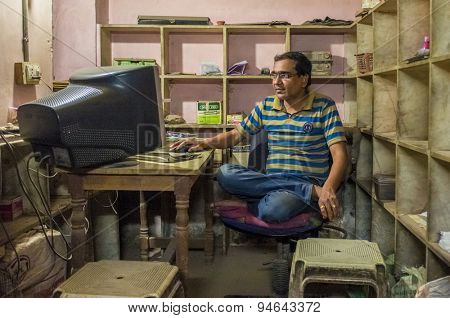 JODHPUR, INDIA - 16 FEBRUARY 2015: Indian man sits in office cross-legged on chair in front of computer screen.
