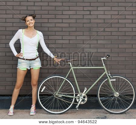 Pretty girl in shorts and t-shirt stands with bicycle fix gear near the brick wall of bright sunny d