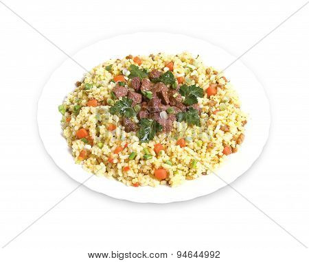 Pilaf with meat and greens on a plate