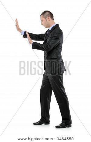 Full Length Portrait Of A Man Pushing Something Imaginary