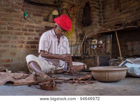 GODWAR REGION, INDIA - 13 FEBRUARY 2015: Elderly Indian shoemaker from Rabari tribe makes new pair of traditional shoes in workshop. Rabari or Rewari are an Indian community in the state of Gujarat.