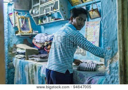 JODHPUR, INDIA - 10 FEBRUARY 2015: Young Indian man irons clothes in home livingroom.