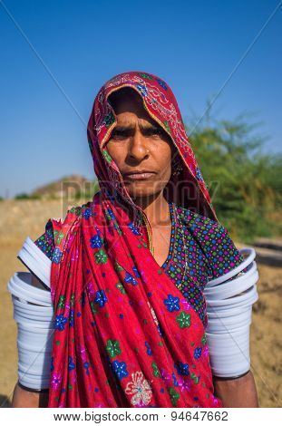 GODWAR REGION, INDIA - 14 FEBRUARY 2015: Rabari tribeswoman stands in field wearing saree and upper-arm bracelets. Rabari are an Indian community in the state of Gujarat.