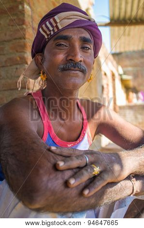 GODWAR REGION, INDIA - 14 FEBRUARY 2015: Mechanic with mustache wearing headscarf and big golden earings sits outside of workshop.