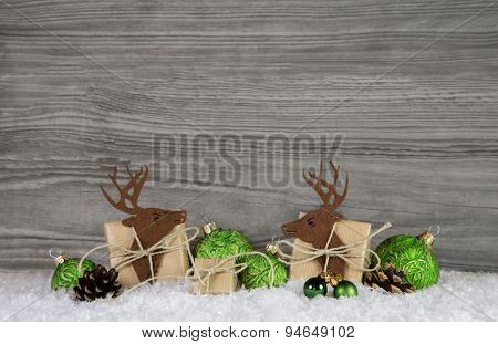 Wooden grey christmas background with reindeer, balls and gifts in green and brown colors.