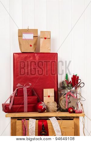 Preparing advent calendar and packing christmas gifts in red colors. Scrapbooking hobby.