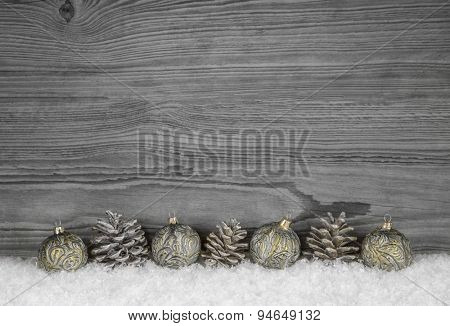 Grey shabby chic christmas background with wood, fir cone and balls in golden color.