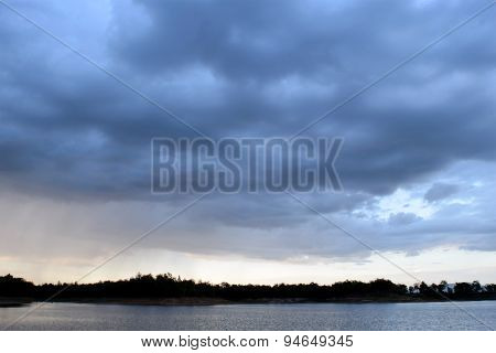 Lake and Dark blue stormy cloudy sky in evening