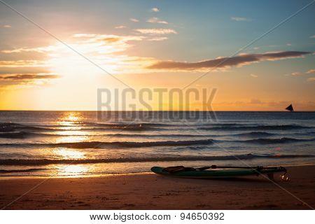 Surfboard on sandy beach