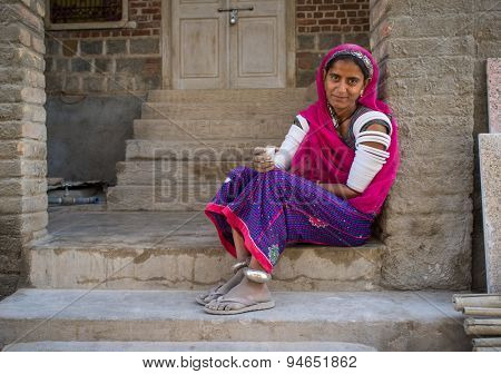 GODWAR REGION, INDIA - 15 FEBRUARY 2015: Indian tribeswoman sits in front of home in saree decorated with upper-arm bracelets.