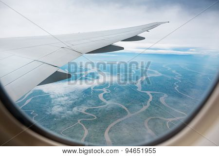 the view from the airplane window to the ground dotted with rivers