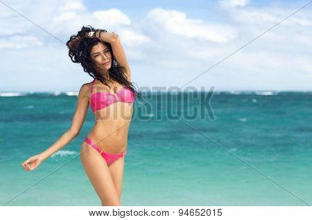 Sexy woman sensual posing  on beach in pink bikini