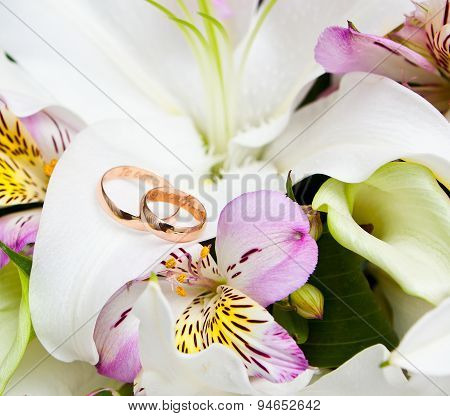 Golden wedding ring on the bride's bouquet.