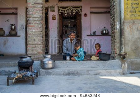 GODWAR REGION, INDIA - 13 FEBRUARY 2015: Father sits after breakfast with children in doorway of courtyard.
