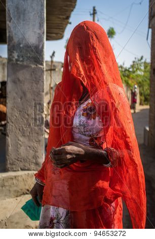 GODWAR REGION, INDIA - 13 FEBRUARY 2015: Indian woman in orange sari with covered head stands in village street.