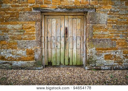 Old rotting weathered wooden double doors in a stone wall