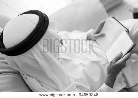 Elderly man sitting and reading book
