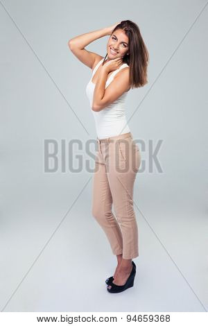 Full length portrait of a happy businesswoman posing over gray background. Looking at camera
