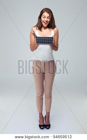 Full length portrait of a cheerful young woman opening gift box over gray background