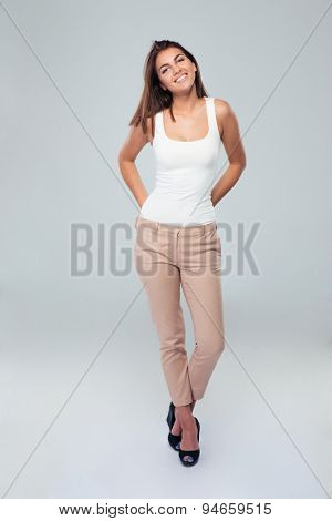 Full length portrait of a casual happy woman standing over gray background. Looking at camera