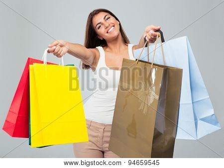 Smiling beautiful woman holding shopping bags over gray background. Looking at camera