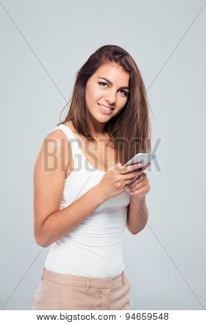 Happy young woman using smartphone over gray background and looking at camera