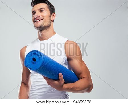 Portrait of a fitness man with yoga mat standing over gray background. Looking away
