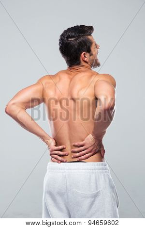 Portrait of a man standing with back pain over gray background