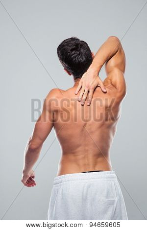 Rear view portrait of a muscular man with neck pain over gray background