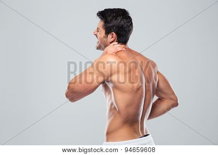 Portrait of a man with neck pain standing over gray background