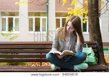 Student Reading Book On Bench