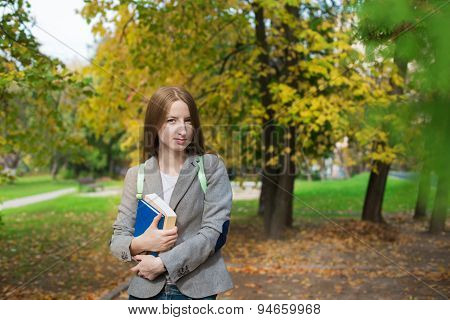 Student Standing With Book In Autumn
