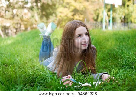 Student Lying On Grass And Thinking