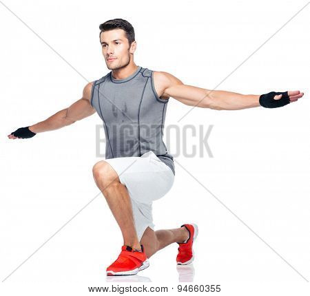 Full length portrait of a sports man stretching isolated on a white background