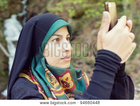 Beautiful Muslim woman with scarf taking mobile photos