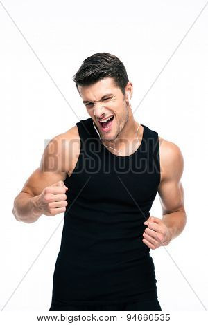 Handsome fitness man listening music in headphones isolated on a white background